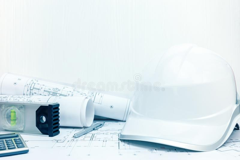 Contractor workplace with spirit level, safety helmet and bluepr. Contractor workplace. spirit level, pencil, calculator, safety helmet and blueprint rolls on royalty free stock image