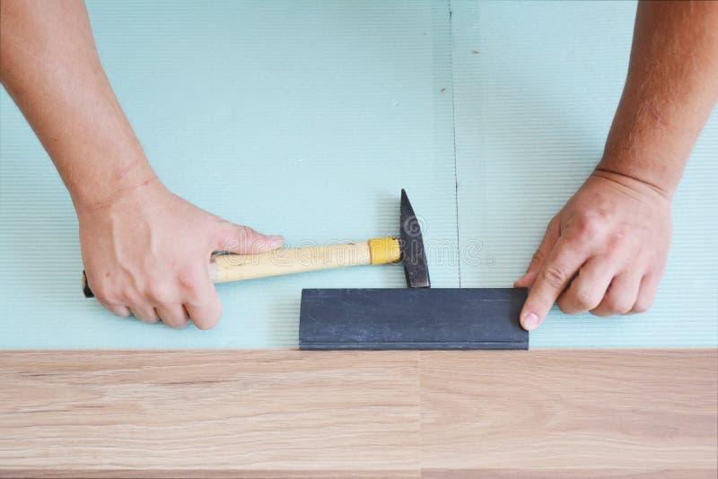 Contractores que instalan suelos laminados de madera con aislamiento y sábanas insonorizadas Suelo de laminado sobre el hombre Ho fotos de archivo