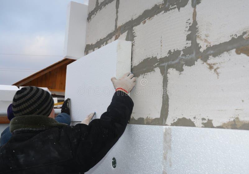 Contractores que instalan una placa de aislamiento de poliestireno en la pared de construcción. Aislamiento en la casa al aire li foto de archivo