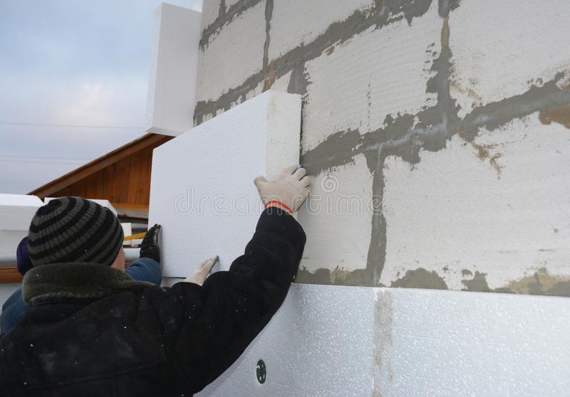 Contractors installing rigid styrofoam insulation board on house construction wall. House insulation outdoors. Contractors installing rigid styrofoam insulation stock photo