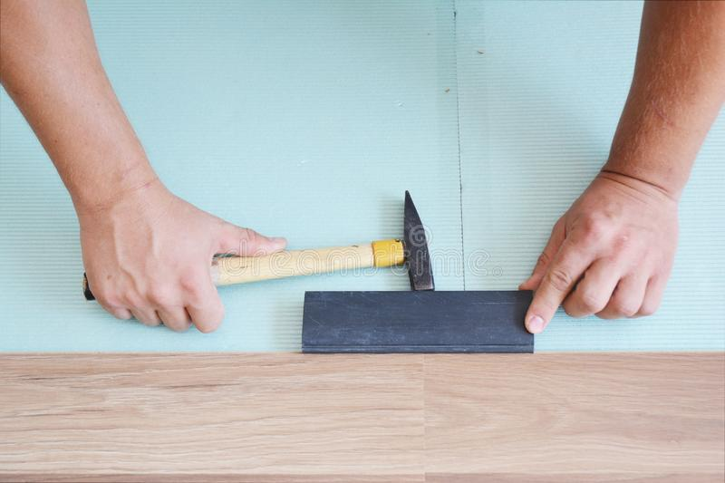 Contractors installing wooden laminate flooring with insulation and soundproofing sheets. Man laying laminate flooring. Man laying. Laminate flooring stock photos