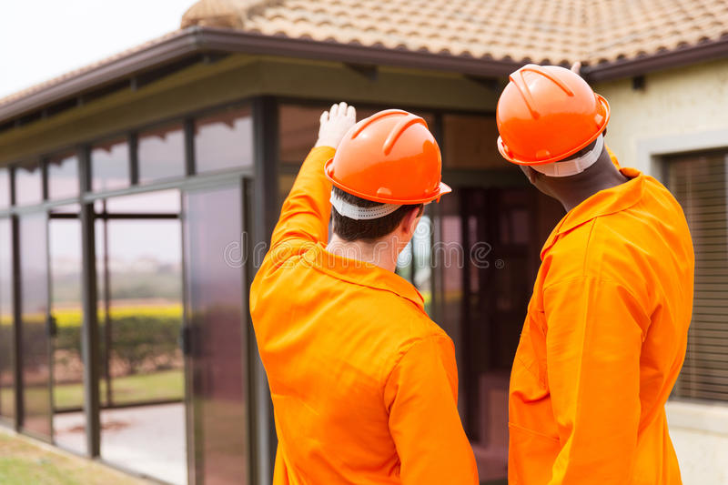 Contractors pointing at house stock photos