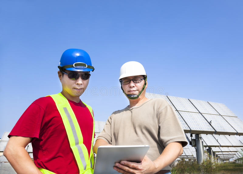 Contractors and standing before solar panels. Two contractors holding tablet pc and standing before solar panel tracking system stock images