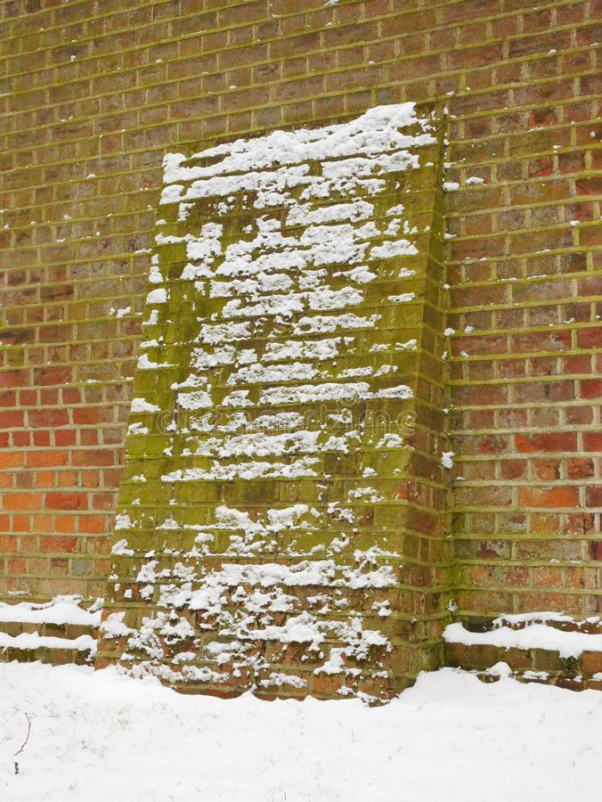 Contrafuerte del ladrillo en la nieve imagenes de archivo