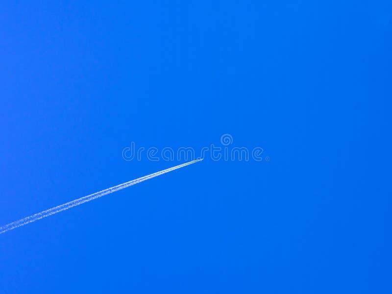 Contrail d'avion contre le ciel bleu clair photos stock