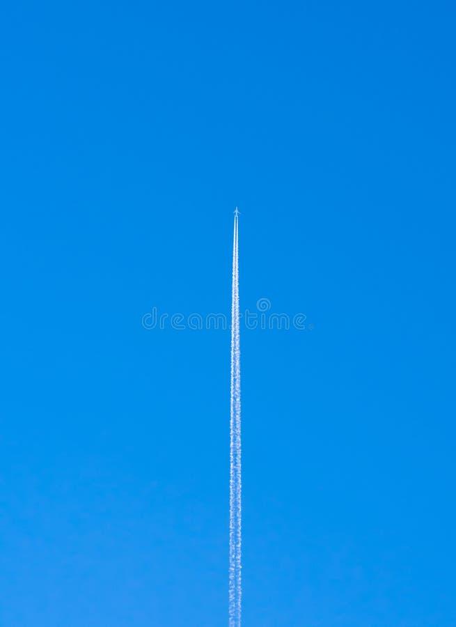 Contrail d'avion contre le ciel bleu clair image stock