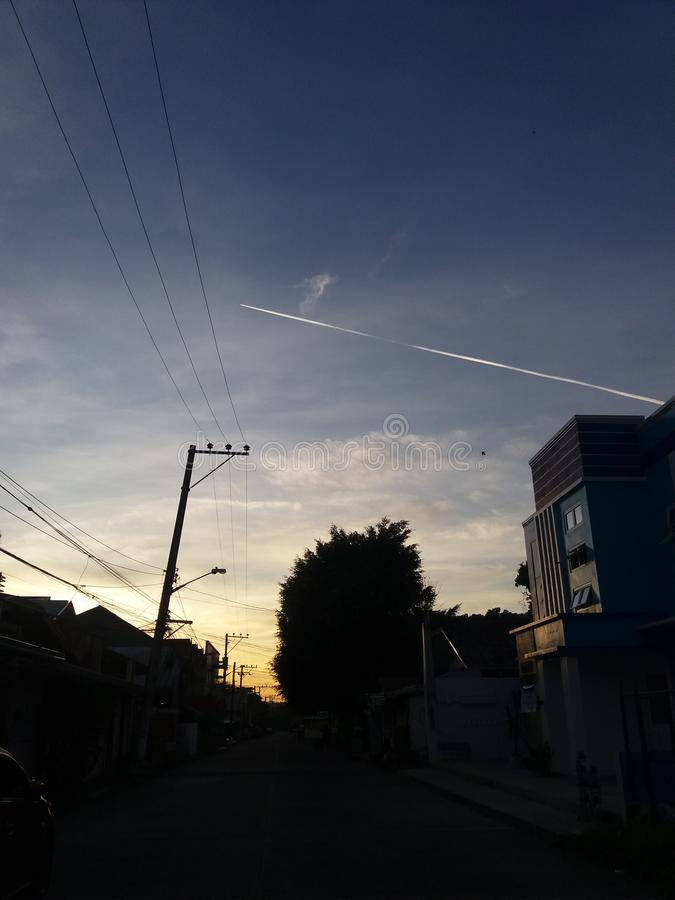 Contrails of a jet plane on a morning sunrise with utility poles viewed from a street. With silhouette of trees and houses royalty free stock image