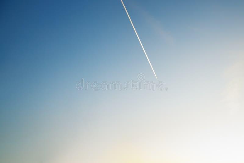 Contrails na zmierzchu jasnego niebie zdjęcia stock
