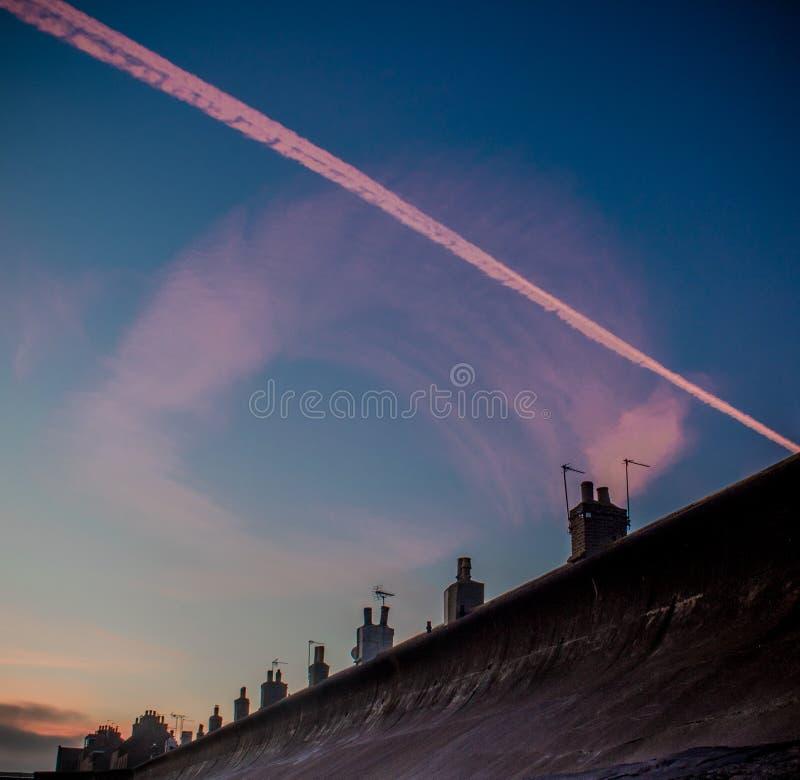 Contrails på soluppgång arkivbild