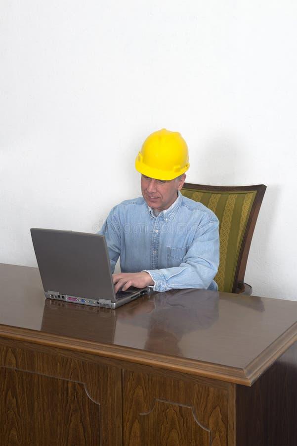 Contramestre ou contratante de loja da fábrica que usa o portátil Co foto de stock