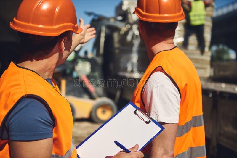 Contramestre profissional que mostra o lugar de construção a seu colega de trabalho fotografia de stock royalty free