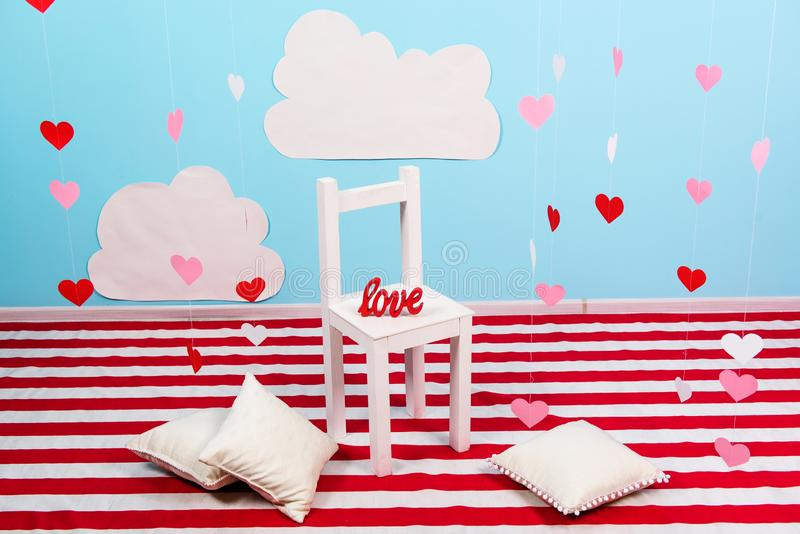 Contransting strings and hearts, a white wooden chair in the centre of the view royalty free stock photos