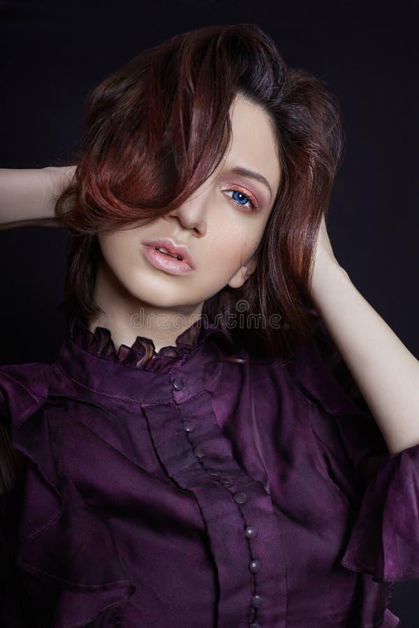Contrapponga il ritratto armeno della donna di modo con i grandi occhi azzurri su un fondo scuro in un vestito porpora Posa splen immagini stock libere da diritti