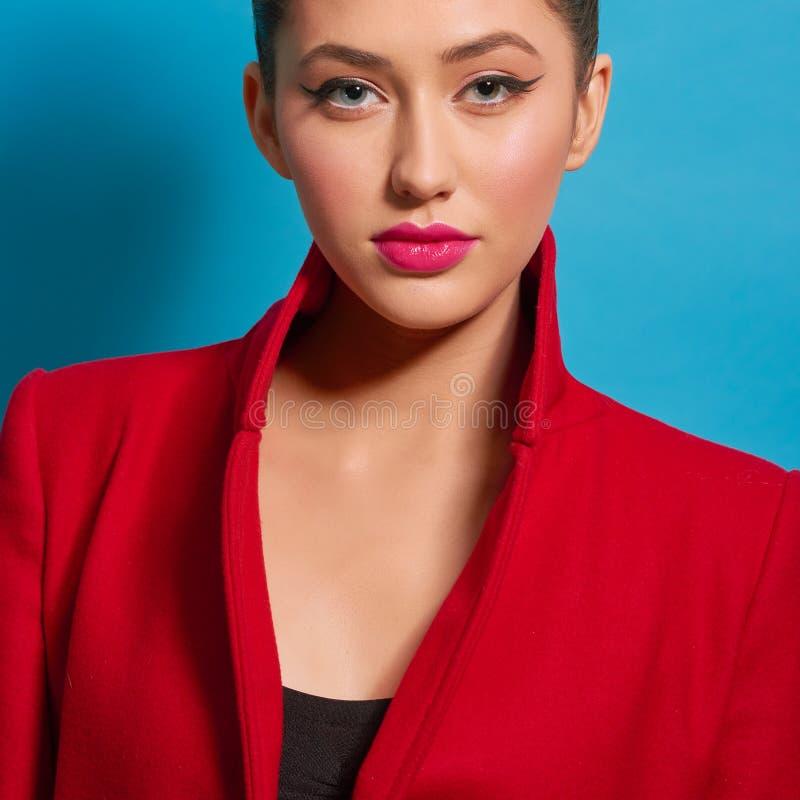 Contrapponga il ritratto di bella ragazza che porta il cappotto rosso luminoso compongono immagini stock libere da diritti