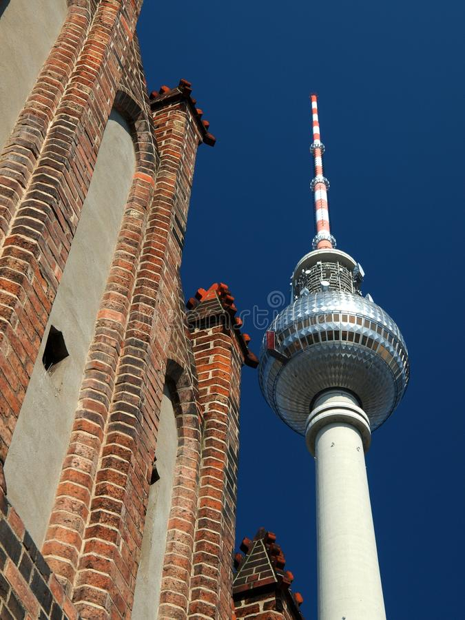 Contrast. An old Kiche and the citizen of Berlin TV tower stock images