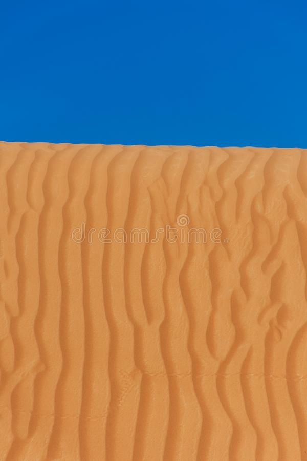 Contrast beautiful deep blue sky and orange rippled pattern sand dunes in the United Arab Emirates. royalty free stock photography