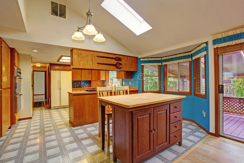 Contrast colors kitchen room. Bright dining area with blue walls, white vaulted ceiling with skylight. View of kitchen island stock image