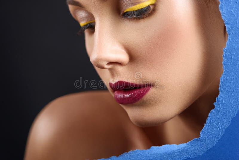 Contrast dichte omhooggaand van het jonge model stellen met blauw verzadigd karton royalty-vrije stock foto's
