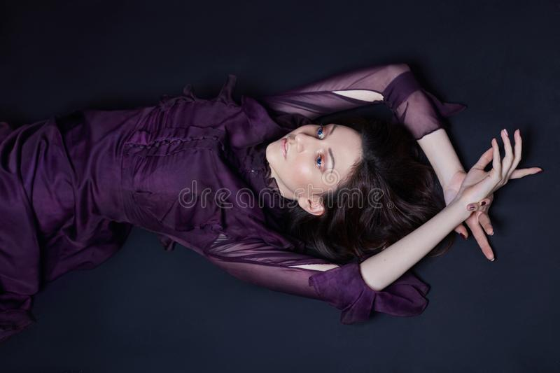 Contrast fashion Armenian woman portrait with big blue eyes lying on the floor in a purple dress. Lovely gorgeous girl posing royalty free stock photos