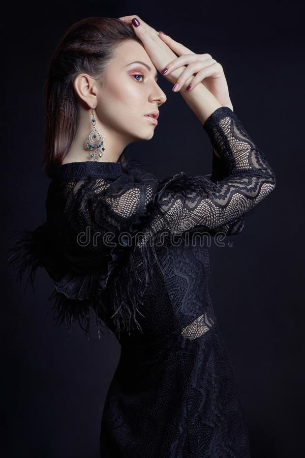 Contrast fashion woman portrait with big blue eyes on a dark background in a black dress. Lovely gorgeous girl posing in evening. Dress. Bright makeup, woman stock image