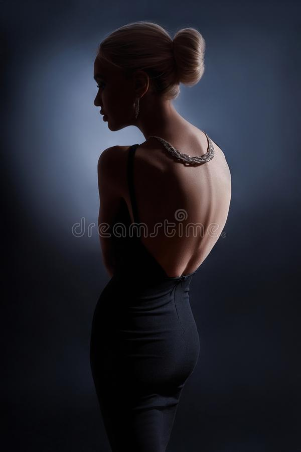 Contrast fashion woman portrait on dark background, the silhouette of a girl with a beautiful curved back. Naked back of a woman royalty free stock image