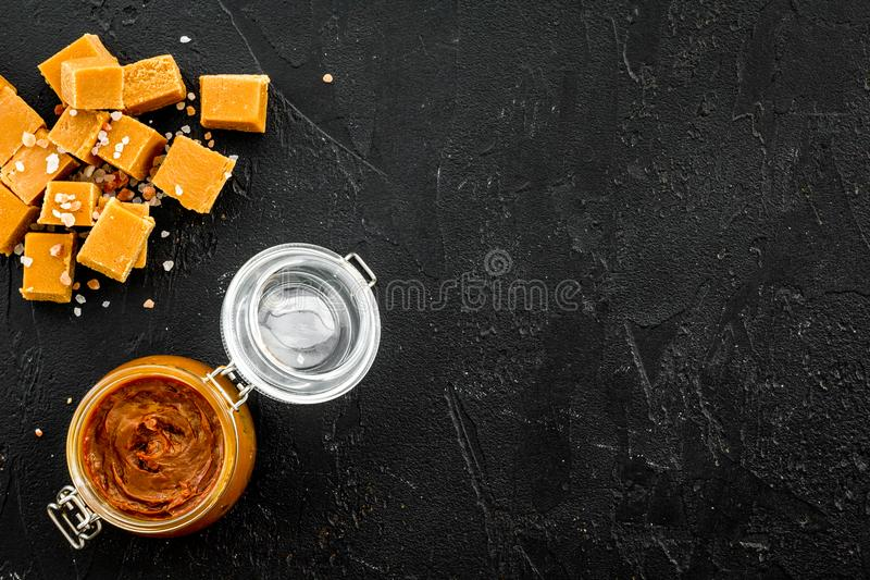 Contrast of flavors. The combination of salty and sweet. Caramel sauce in glass jar near caramel cubes on black. Background top view royalty free stock images