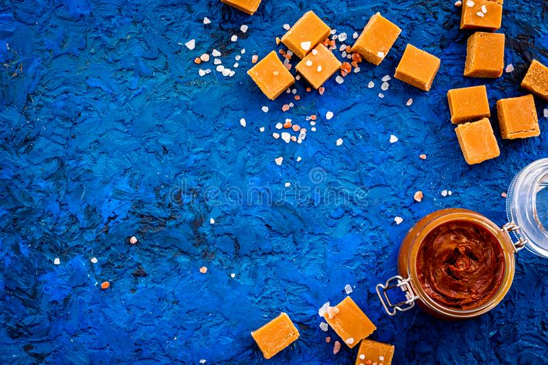 Contrast of flavors. The combination of salty and sweet. Caramel sauce in glass jar near caramel cubes on blue. Background top view stock photo