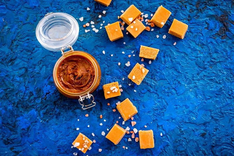 Contrast of flavors. The combination of salty and sweet. Caramel sauce in glass jar near caramel cubes on blue. Background top view stock photos