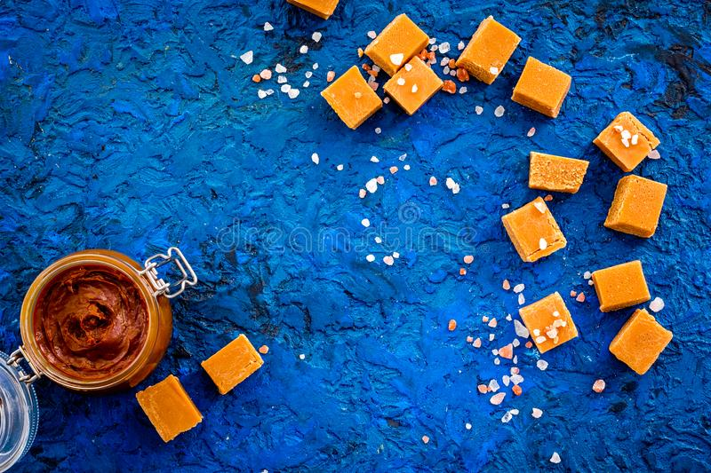 Contrast of flavors. The combination of salty and sweet. Caramel sauce in glass jar near caramel cubes on blue. Background top view stock image