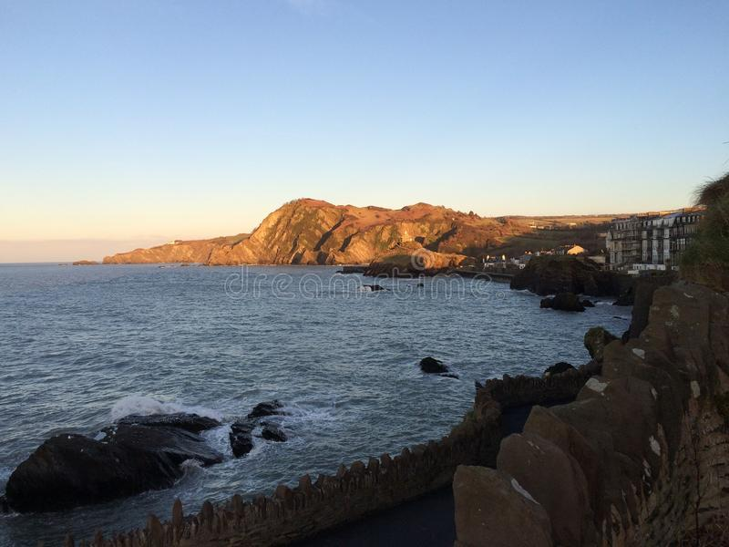 Contrast of foreground and background. Sunset on Ilfracombe harbour, coastline is royalty free stock photos