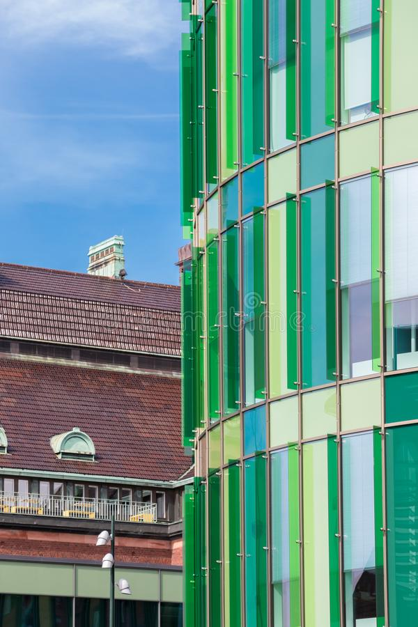 Contrast between a green glass facade of a modern building in front of another traditional old building royalty free stock image