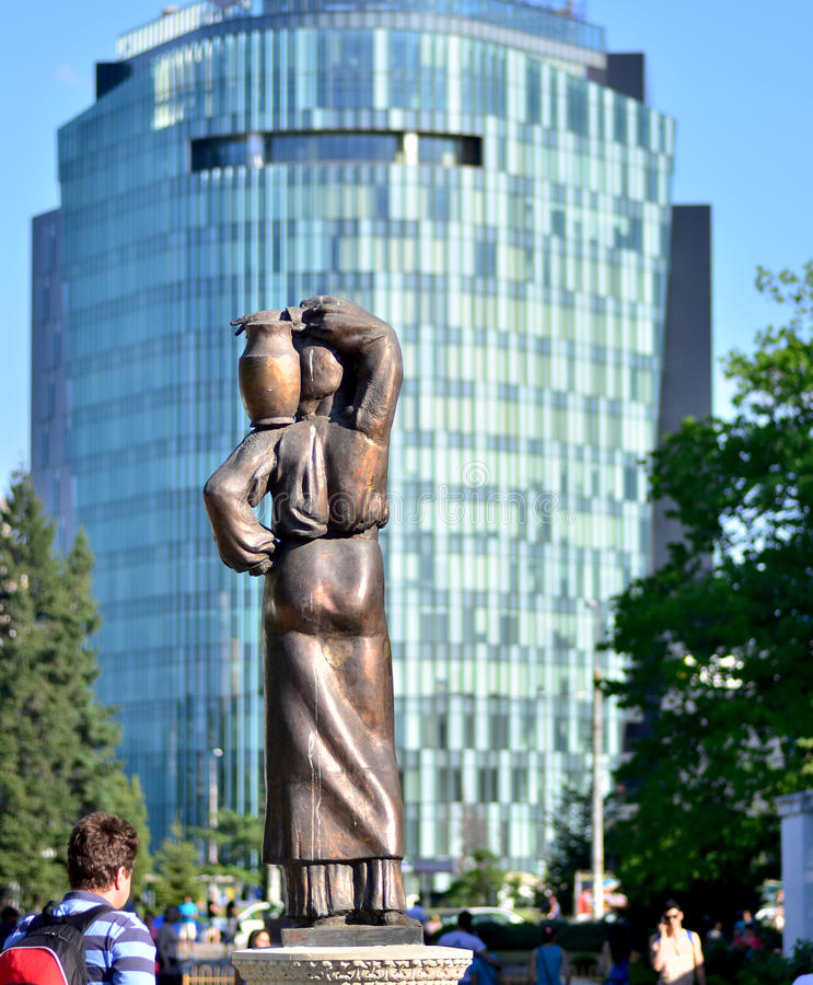 Contrast in Herastrau Park. Herastrau Park, Bucharest - the main entrance and a detail of a statue representing a peasant women carrying a pitcer, in background stock photos