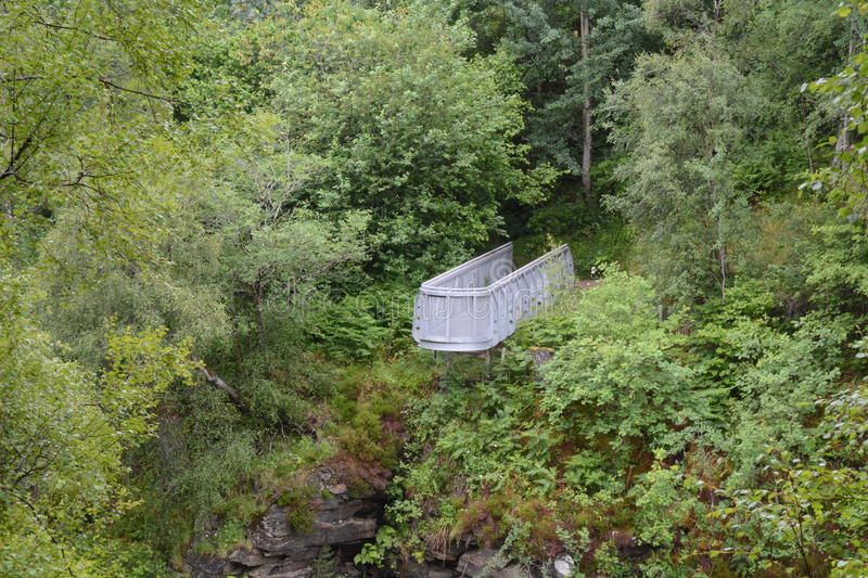 Contrast between Metal Viewpoint and Vegetation. A galvanised steel metal structure overhangs a gorge. Surrounded by lush green vegetation of birch trees, rowan royalty free stock photography