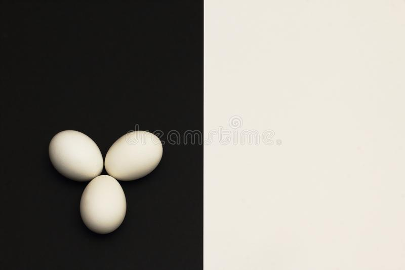 White chicken eggs on black part of contrasting black and white background. Minimalism style royalty free stock image