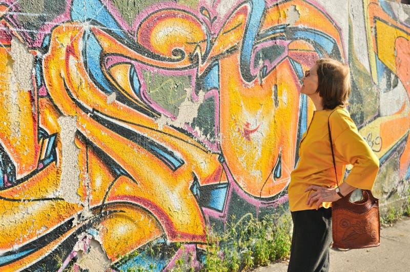 Contrast - modern versus senior lady. Senior woman looking at colourful graffiti wall royalty free stock photos