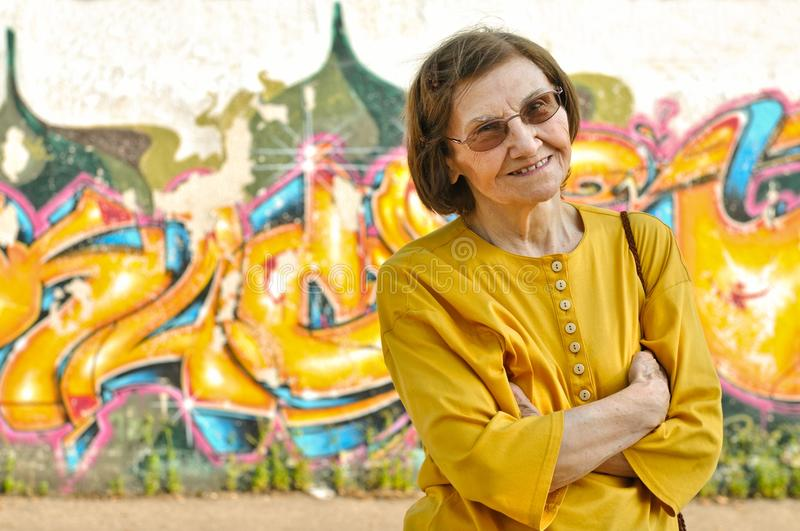 Contrast - modern versus senior lady. Senior woman standing at colourful graffiti wall royalty free stock photography
