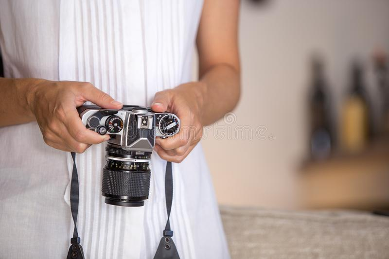 Contrast between old and modern times: a young woman with a vintage camera around her neck fiddles with her smartphone stock image