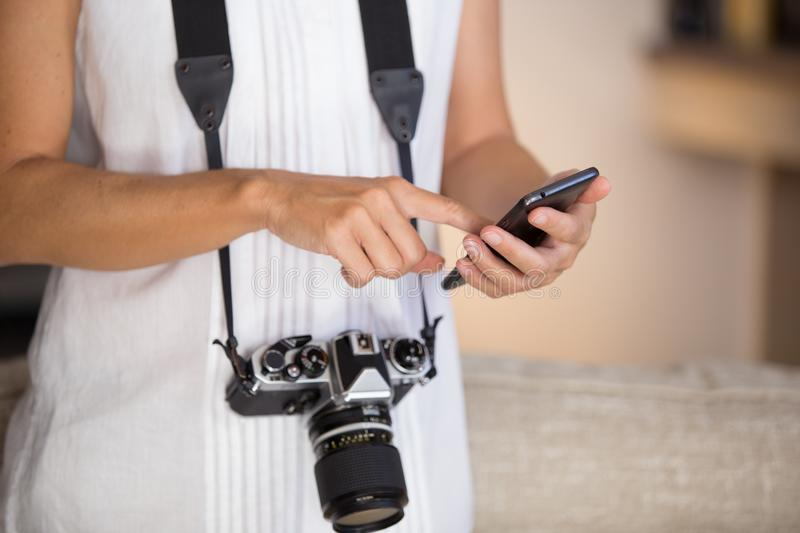 Contrast between old and modern times: a young woman with a vintage camera around her neck fiddles with her smartphone stock photo
