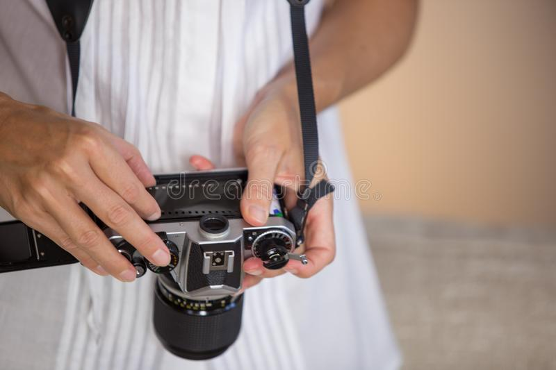 Contrast between old and modern times: a young woman with a vintage camera around her neck fiddles with her smartphone royalty free stock photography