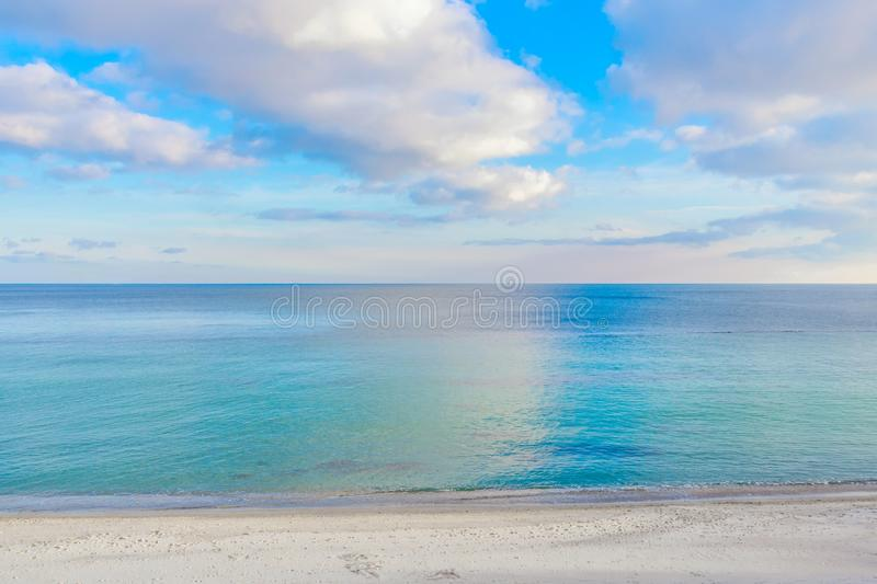 Contrast photo of the sea and cloudy sky. Clouds reflected in water. Footprints on coastal sand stock photography
