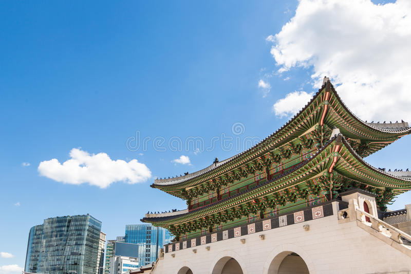 Contrast in Seoul. The traditional architecture of the gate of the Royal Palace in Seoul contrasts with the modern office buildings outside its wall royalty free stock photography