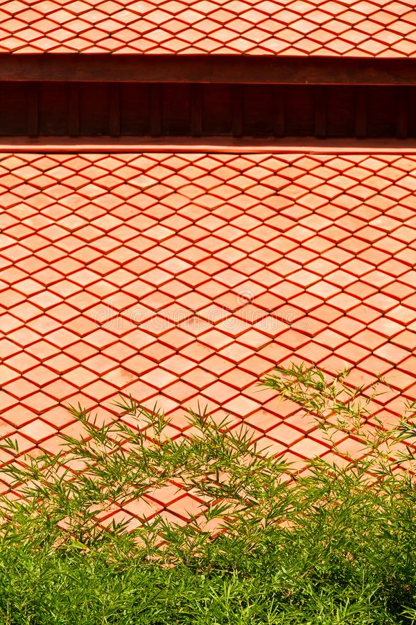 Thai traditional orange color ceramic tile style and green color bamboo royalty free stock images