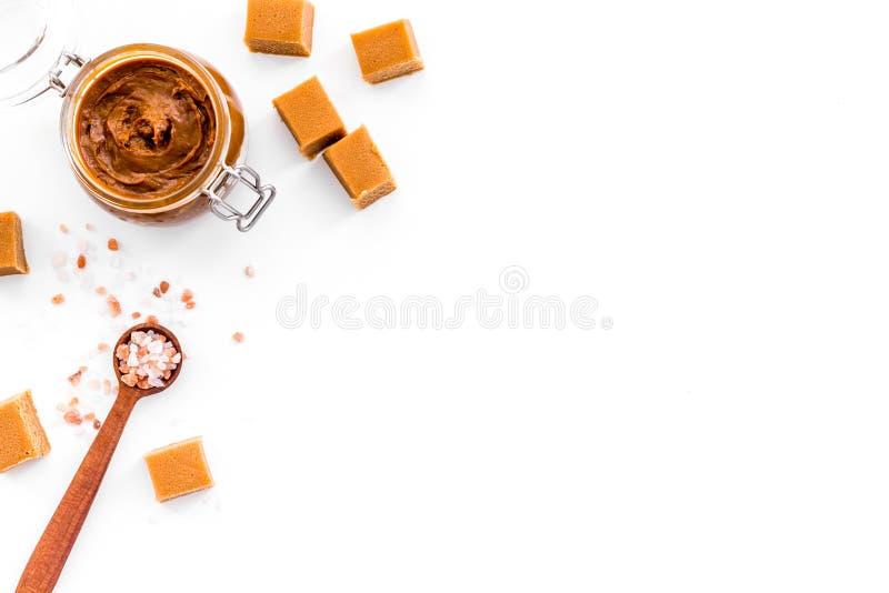 Contrast van aroma's De combinatie zout en zoet Karamelsaus in glaskruik dichtbij karamelkubussen op wit royalty-vrije stock afbeelding