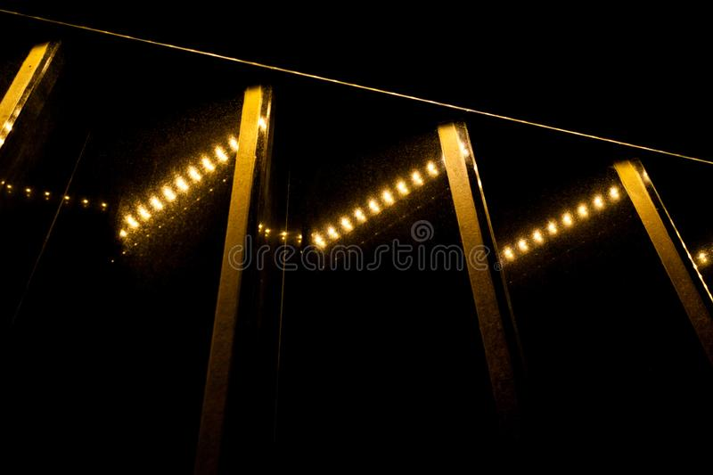 Contrast of yellow lights and stripes and black background. Lighting abstract. Contrast of yellow lights and stripes and black background royalty free stock photos