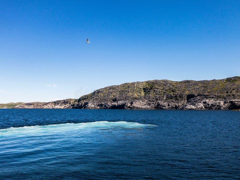 Contraste la bella escena con la isla verde entre la bahía del mar y el cielo azul imagenes de archivo