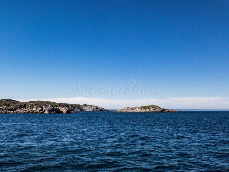 Contraste la bella escena con la isla verde entre la bahía del mar y el cielo azul imágenes de archivo libres de regalías