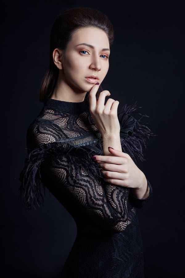 Contraste o retrato da mulher da forma com olhos azuis grandes em um fundo escuro em um vestido preto Menina lindo bonita que lev imagens de stock royalty free