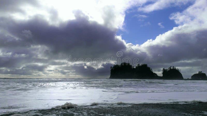 Contraste radical des piles de mer près de la plage avec le ciel bleu photos stock