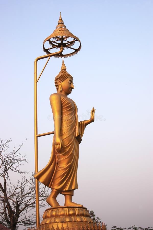 Contraste spectral d'or de Bouddha avec le ciel et les nuages image libre de droits