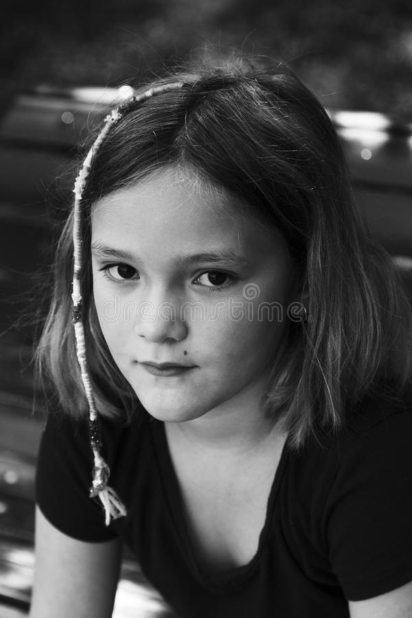 Contrasted black and white vertical close up of pretty little girl. In dark shirt with hippie style cotton hair braid royalty free stock photography